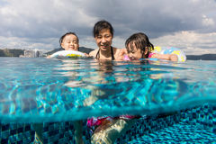 Asian Chinese family playing at the outdoor swimming pool Stock Photos