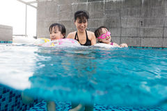 Asian Chinese family playing at the outdoor swimming pool Stock Photo