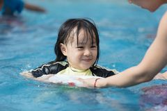 Asian Chinese family playing in swimming pool. Outdoor Royalty Free Stock Photos