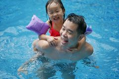 Asian chinese father and daughter having fun in swimming pool royalty free stock photography