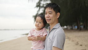 Asian chinese father holding his daughter by the seaside Stock Images