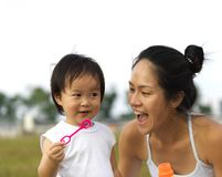 Asian chinese female parent blowing bubbles with baby girl. Asian chinese female parent bonding with child through games Stock Photo
