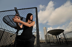 Asian Chinese Girl carrying a Pistol Royalty Free Stock Image