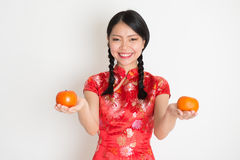 Asian chinese girl holding tangerine Royalty Free Stock Images