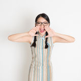 Asian Chinese girl  shouting loud. Portrait of Asian Chinese girl  shouting loud, hands next to the mouth, in retro revival style cheongsam standing on plain Royalty Free Stock Photo