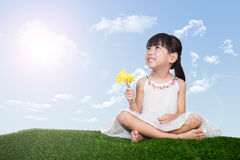 Asian Chinese girl sitting on the grass and holding flowers Royalty Free Stock Images