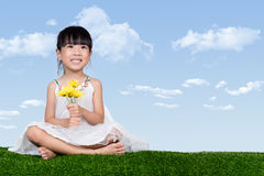 Asian Chinese girl sitting on the grass and holding flowers Royalty Free Stock Photography