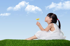 Asian Chinese girl sitting on the grass and holding flowers Stock Photo
