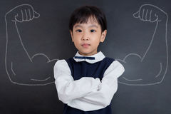 Asian Chinese girl standing against blackboard with sketched strong arms. Asian Chinese little girl standing against blackboard with sketched strong and muscled royalty free stock images