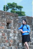 Asian Chinese girls wear student clothes in Republic of China. In an ancient town, stand by an old stone wall, pretty beautiful girl, classic student clothes royalty free stock photography