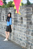Asian Chinese girls wear student clothes in Republic of China. In an ancient town, stand by an old stone wall, pretty beautiful girl, classic student clothes royalty free stock photo
