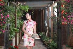 Asian Chinese girls wears cheongsam enjoy free time in ancient town. Asian Chinese girls wear cheongsam, in an ancient town, traditional cloth, made of silk stock image