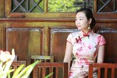 Asian Chinese girls wears cheongsam enjoy free time in ancient town. Asian Chinese girls wear cheongsam, in an ancient town, traditional cloth, made of silk royalty free stock photos