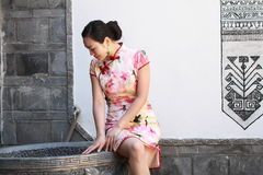 Asian Chinese girls wears cheongsam enjoy free time in ancient town. Asian Chinese girls wear cheongsam, in an ancient town, traditional cloth, made of silk royalty free stock images