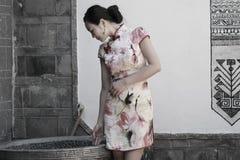 Asian Chinese girls wears cheongsam enjoy free time in ancient town. Asian Chinese girls wear cheongsam, in an ancient town, traditional cloth, made of silk royalty free stock image