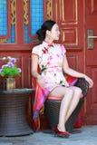 Asian Chinese girls wears cheongsam enjoy holiday in ancient town. Asian Chinese girls wear cheongsam, in an ancient town, traditional cloth, made of silk royalty free stock photo
