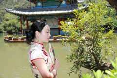 Asian Chinese girls wears cheongsam enjoy holiday in lijiang ancient town. Asian Chinese girls wear cheongsam, in an ancient town, traditional cloth, made of stock photography