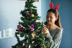 Asian Chinese happy girl with reindeer costume decorate gifts on Xmas tree. Attractive cute woman celebrate Christmas holiday in. Asian Chinese happy girl with stock images