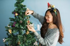 Chinese girl decorate gift on Christmas tree. Asian Chinese happy womanl with small santa costume decorate gifts on Xmas tree. Attractive cute girl celebrate royalty free stock images