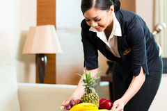 Asian Chinese hotel housekeeper placing fruit. Asian Chinese hotel executive housekeeper placing fruit treatment to welcome arriving VIP guests stock photos