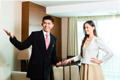Asian Chinese hotel manager presenting suite. Asian Chinese Hotel Manager or director or supervisor presenting arriving VIP guests the room or suite Stock Images