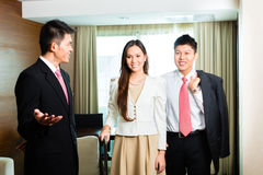 Asian Chinese hotel manager presenting suite royalty free stock photos
