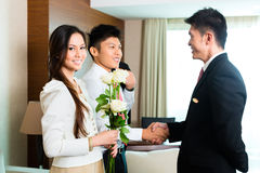 Asian Chinese hotel manager welcome VIP guests. Asian Chinese Hotel Manager or director or supervisor welcome arriving VIP guests with roses on arrival in luxury Stock Photography
