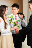 Asian Chinese hotel manager welcome VIP guests. Asian Chinese Hotel Manager or director or supervisor welcome arriving VIP guests with roses on arrival in luxury Royalty Free Stock Photography