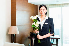 Asian Chinese hotel manager welcomes arriving VIP guests. Hotel Manager or director or supervisor welcome arriving VIP guests with roses on arrival in luxury or Stock Image