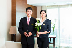 Asian Chinese hotel manager welcoming VIP guests. Hotel Manager or director and supervisor welcome arriving VIP guests with roses on arrival in luxury or grand Stock Photography