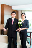 Asian Chinese hotel manager welcoming VIP guests. Hotel Manager or director and supervisor welcome arriving VIP guests with roses on arrival in luxury or grand Royalty Free Stock Photo