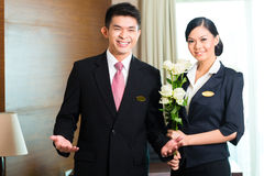 Asian Chinese hotel manager welcoming VIP guests stock photography