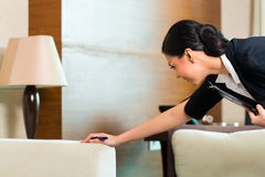 Asian Chinese housekeeper controlling hotel room. Housekeeping manager or assistant controlling or checking the room or suit of a hotel with a checklist on Royalty Free Stock Images