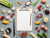 Asian chinese ingredients, copy space. Asian ingredients and clipboard with white paper sheet. Various of Chinese cooking ingredients and chopsticks on gray royalty free stock photography
