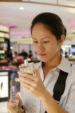 Asian chinese lady assessing her purchase in Duty Free. Picture of asian chinese lady testing out her purchase in duty free. Asian chinese tourists are flooding Royalty Free Stock Images