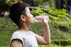 Asian Chinese little boy drinking mineral water. At outdoor park stock image