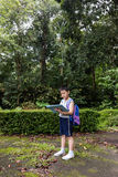 Asian Chinese little boy holding map in the forest Royalty Free Stock Image