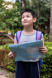 Asian Chinese little boy holding map in the forest Stock Images