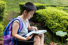 Asian Chinese little boy holding map sitting in the forest Stock Photos