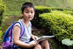 Asian Chinese little boy holding map sitting in the forest Royalty Free Stock Photo