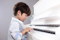 Asian Chinese little boy playing piano at home Royalty Free Stock Photo