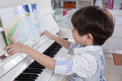 Asian Chinese little boy playing piano at home Royalty Free Stock Photos