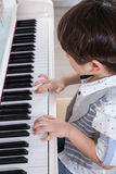 Asian Chinese little boy playing piano at home Stock Photos