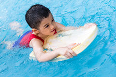 Asian Chinese Little Boy Swimming With Floating Board. At Outdoor Swimming Pool stock photography