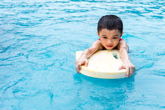 Asian Chinese Little Boy Swimming With Floating Board. At Outdoor Swimming Pool stock photo