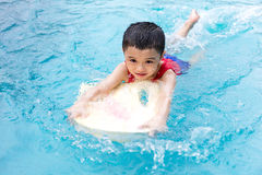 Asian Chinese Little Boy Swimming With Floating Board. At Outdoor Swimming Pool stock image