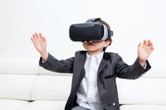 Asian Chinese little boy wearing virtual reality headset at home. Asian Chinese little boy wearing virtual reality headset sitting on the sofa at home Stock Photography