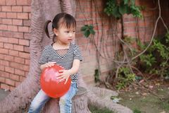 Happy little cute lovely girl Chinese child smile laugh play red balloon have fun at summer park nature happiness childhood. Asian Chinese little cut lovely girl stock images