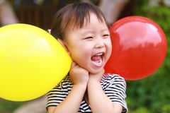 Happy little cute lovely girl Chinese child smile laugh play colorful balloon have fun at summer park nature happiness childhood. Asian Chinese little cut lovely royalty free stock images