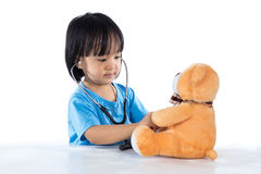 Asian Chinese little doctor girl examine teddy bear Royalty Free Stock Photography